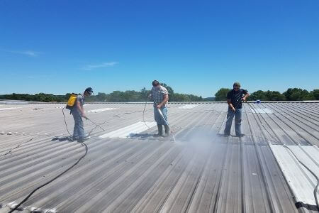 Three men pressure washing metal roof on commercial building.