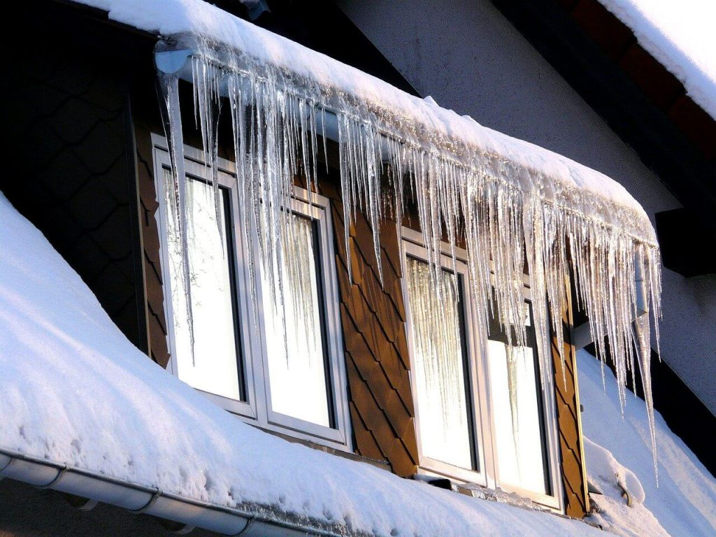 Snow and ice hanging from the gutter over the gables of a home.